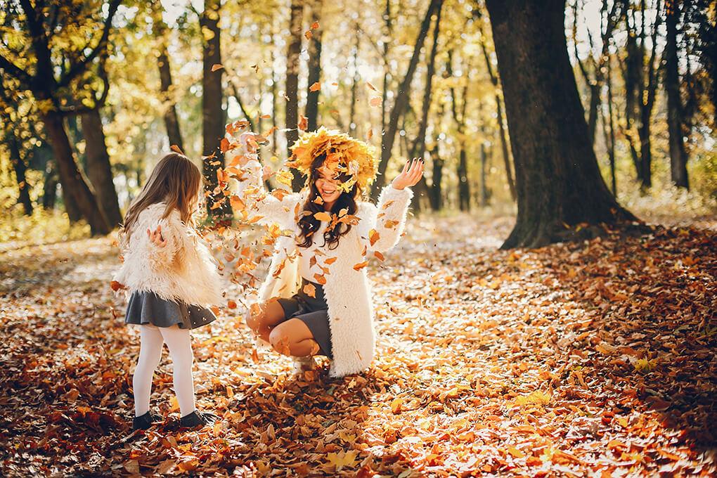 Madre e hija jugando en un bosque en otoño